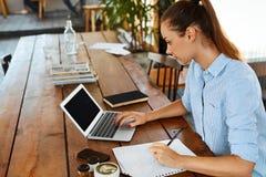 学会,学习 使用便携式计算机的妇女在咖啡馆,运作 库存图片