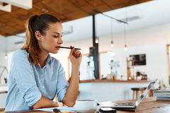 学会,学习 使用便携式计算机的妇女在咖啡馆,运作 库存照片