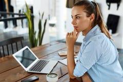 学会,学习 使用便携式计算机的妇女在咖啡馆,运作 免版税库存照片
