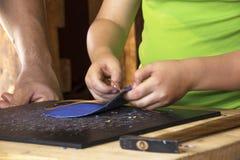 学会年轻的男孩与皮革一起使用 库存图片