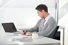 学员与膝上型计算机一起使用在服务台 免版税图库摄影