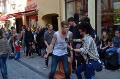 学员作用吉他和唱歌。 街道音乐日 免版税库存照片