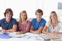 学员坐和查看照相机的一个微笑的组 免版税库存图片