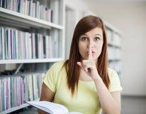 学员女孩在图书馆里 免版税库存照片