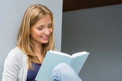 学员女孩坐的阅读书外面 免版税图库摄影