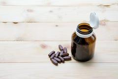 医学在棕色玻璃瓶投入了板台木头和 免版税图库摄影