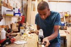 学徒飞行的木头在木匠业车间 免版税图库摄影