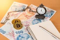 学报、笔、怀表和两金黄bitcoins在土耳其钞票 免版税图库摄影