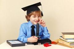 学术帽子的小微笑的男孩有在他的书桌的显微镜的 免版税库存图片