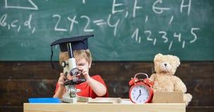 学术盖帽的孩子男孩与显微镜一起使用在教室,在背景的黑板 繁忙的面孔的孩子在显微镜附近 库存图片