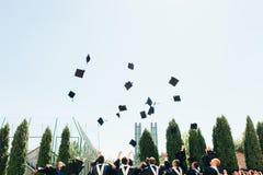 学术礼服的成功的毕业生,扔他们的帽子,去 免版税图库摄影