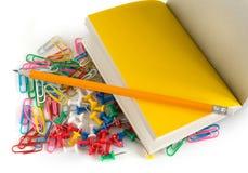 学校办公室辅助部件,铅笔,按钮,笔记薄,五颜六色的纸夹,在被隔绝的白色背景 库存照片