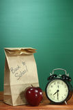 学校午餐、苹果计算机和时钟在书桌上在学校 库存照片