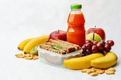 学校午餐用三明治、新鲜水果、薄脆饼干和汁液 免版税库存照片