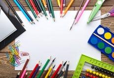 学校在木背景的文具框架:纸,铅笔,刷子,剪刀,文件夹,算盘, 免版税库存照片