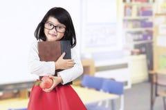 学校女孩拿着书和苹果在类 免版税库存图片