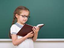 学校女孩读了书,摆在校务委员会,空的空间,教育概念 免版税库存照片