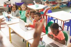 学校孩子行正面图听他们老师和他们中的一个举他的手指answe的 免版税库存照片