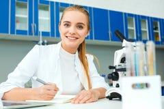 学校实验室工作场所文字项目的年轻化学老师 图库摄影