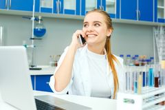 学校实验室工作场所电话的年轻化学老师 免版税库存图片