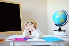 学校工作场所的疲乏的小男孩 免版税图库摄影
