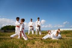 学校教师和孩子空手道教训的在海附近 免版税库存图片
