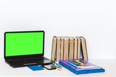学校文具辅助部件-笔记本,习字簿,绿色屏幕膝上型计算机,塑料文件夹,笔,玻璃,纸夹,贴纸, 免版税图库摄影