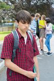 学校朋友说闲话的不快乐的男孩 免版税库存图片