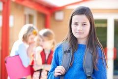 学校朋友说闲话的不快乐的女孩 库存图片