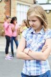 学校朋友说闲话的不快乐的女孩 免版税库存图片