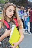 学校朋友说闲话的不快乐的女孩 图库摄影