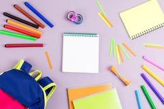 学校概念舱内甲板位置 哄骗背包,笔记本,在木桌面上的标志 免版税库存照片