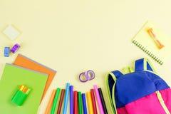 学校概念舱内甲板位置 哄骗背包,笔记本,在木桌面上的标志 免版税库存图片