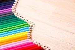 学校用品上色了形成波浪,在木背景的铅笔 库存图片