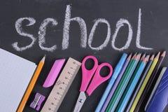 学校用品书、笔匣、铅笔在玻璃和一个笔记本在一个校务委员会的背景与题字 库存图片