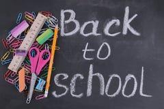 学校用品书、笔匣、铅笔在玻璃和一个笔记本在一个校务委员会的背景与题字 免版税图库摄影