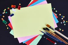 学校用品和色纸空白纸在黑背景的与文本的拷贝空间 免版税库存图片