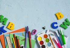 学校用品和辅助部件在蓝色背景 文本的空位 顶视图 免版税库存图片