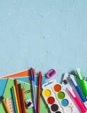 学校用品和辅助部件在蓝色背景 文本的空位 顶视图 免版税图库摄影