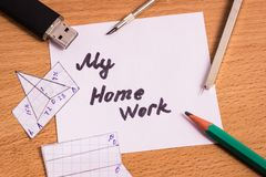 学校用品在题字附近放我的家庭作业 图库摄影