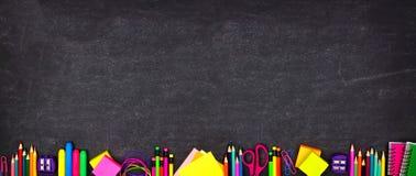 学校用品底下边界横幅,在黑板背景的顶视图与拷贝空间 r 免版税库存照片