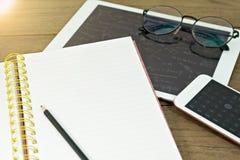 学校用品是一块铅笔、书、片剂和玻璃在书桌上 库存照片