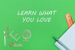 学校用品木缩样和笔记本有文本的学会什么您在绿色背景爱 免版税库存照片