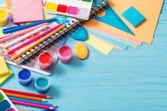 学校用品的汇集在蓝色木背景的 免版税库存图片