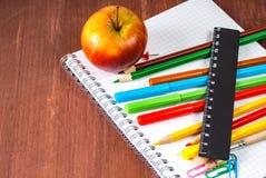 学校用品-笔记本,笔,在木背景的铅笔 免版税图库摄影