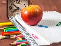 学校用品-笔记本,笔,在木背景的铅笔 库存照片