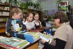 学校的学生在学校图书馆里接受课本 免版税库存图片