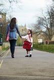 学校的母亲走的女儿沿道路 库存图片