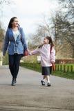 学校的母亲走的女儿沿道路 免版税库存图片