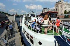 学校的毕业生在莫斯科河的游览中的游船的 免版税库存照片